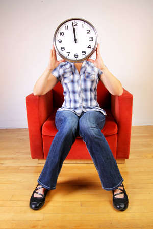 Woman sitting in a orange sofa holding a clock set at midday or midnight in front of her face Banco de Imagens