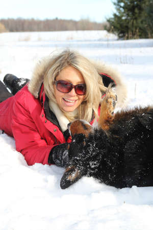 Woman playing with a dog in snow during a nice winter day Stock Photo - 12579060