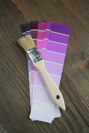Brush with wood handle on a purple color palette photo