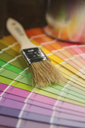Brush with wood handle on a color palette and painting in background Stock Photo