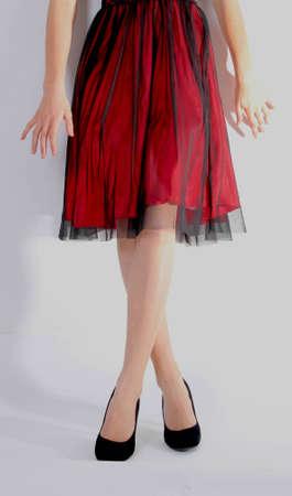 velvet dress: bottom of a woman wearing red dress and black velvet shoes Stock Photo