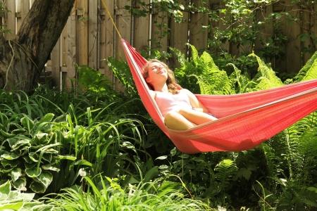 赤いハンモックで横たわっている若い女の子