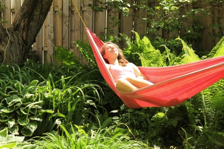 Young girl lying down in a red hammock