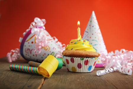 Birthday cupcake with candle and birthday hats in background Imagens