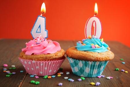 オレンジ色の背景に青とピンクのカップケーキ上 40 の誕生日の蝋燭を数します。