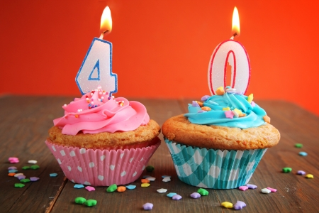 Number forty birthday candles on a blue and pink cupcake on a orange background