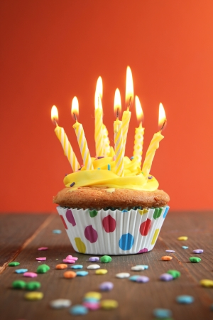birthday cupcake: Cupcake with yellow icing full of yellow candles on orange background