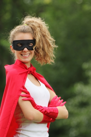 supergirl: smilling blond and young woman with a mask and red super hero kit