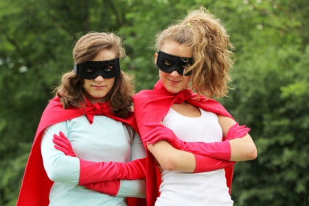 Super team of super heros girl with red cape and red gloves photo