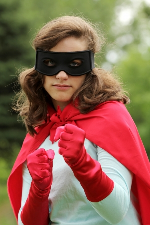 supergirl: Serious young woman wearing a red super hero kit with a black mask is ready to attack