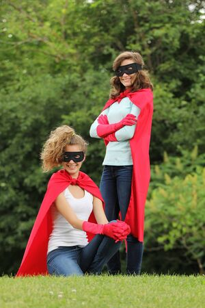 supergirl: Super team of super heros girl with red cape and red gloves outside in a forest