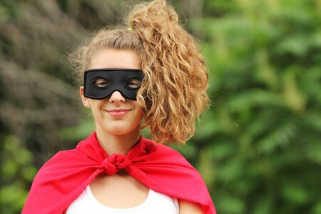 smilling young woman with pony tail wearing a red super hero kit photo