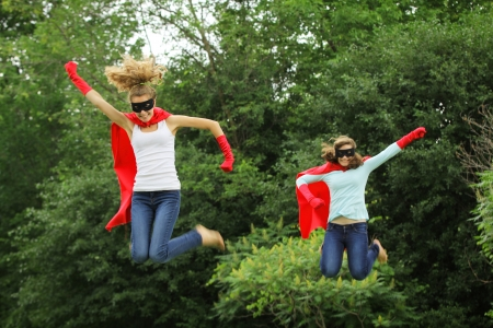 Super team of super heros girl with red cape, red gloves and black mask jumping in the air photo
