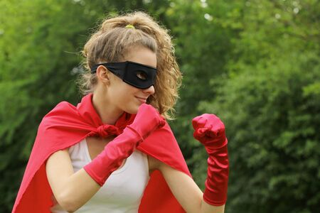 Blond super hero with red cape and red gloves is ready to fight photo