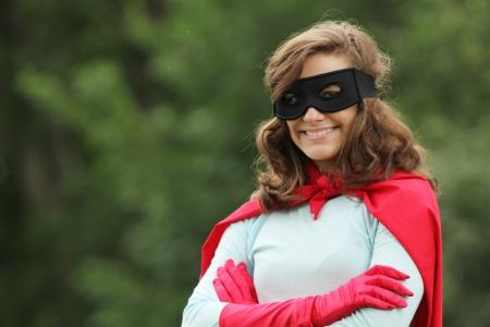 super human: Mujer joven con rojo s�per h�roes kit sonriendo Foto de archivo