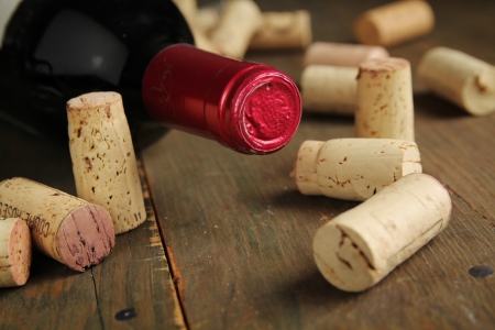 Cork wine on a wooden table with a bottle of red wine