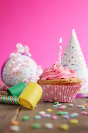 Birthday cupcake with candle and birthday hats in background photo