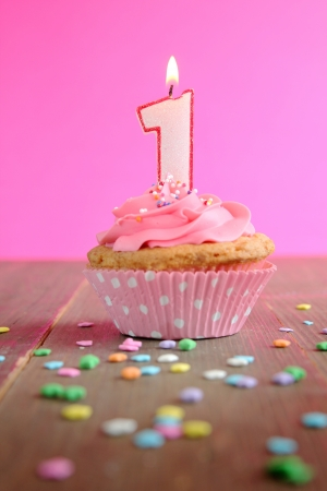 one item: Number one birthday candle on a pink cupcake on a wooden table