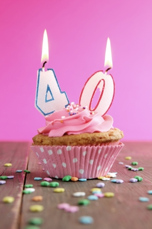 Number forty birthday candles on a pink cupcake on a wooden table Banco de Imagens
