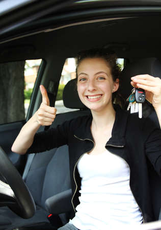 Proud teenager with key car in hand in a car