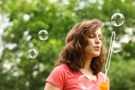 Brunette girl doing bubble soap outside in a park Stock Photo - 14622760