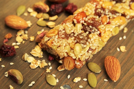 Organic granola bar with nuts and dry fruits on a wooden table Banco de Imagens
