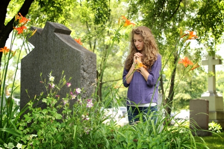 Girl with closed eyes pray in front of a tomb in a cemetery Stock Photo