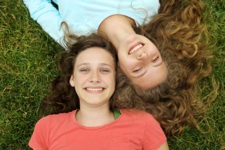 公園の芝生の上に横たわってティーンエイ ジャー友達に笑顔
