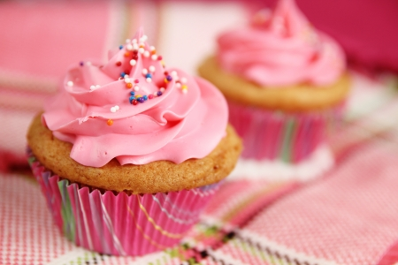 Pink cupcake with candies on a checkered tablecloth photo