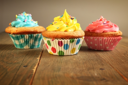Three different colors cupcakes on a wooden table, blue, yellow and pink