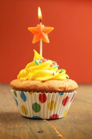 木製のテーブルの 3 つ星の誕生日の蝋燭を持つ黄色のカップケーキ