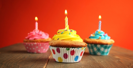 Three cupcake of different colors with birthday candle on a wooden table photo