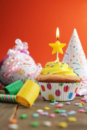 Birthday cupcake with star candle and birthday hats on an orange background photo