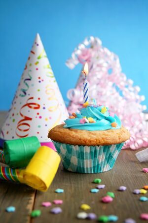 Birthday cupcake with candle and birthday hats on a blue background photo