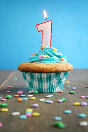 one year: Number one birthday candle on a blue cupcake on blue background Stock Photo
