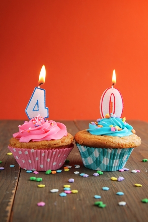 Number forty birthday candles on a pink and blue cupcake on a wooden table Banco de Imagens