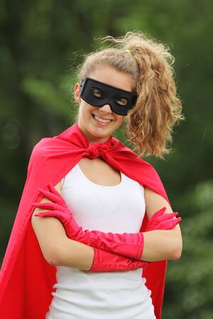 Blond girl wearing a red superhero uniform and a black mask smiling photo