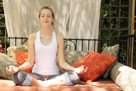Relaxing teenager doing yoga, outside on a couch full of cushions photo