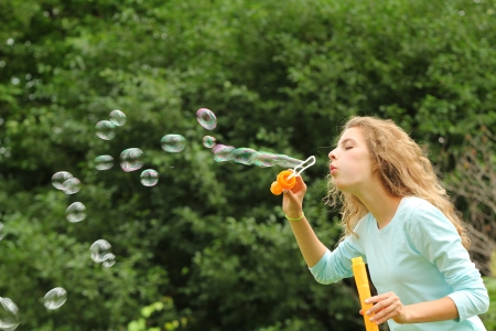Blond girl doing huge bubble soap outside in a park Stock Photo - 14726392