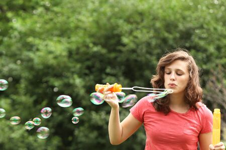 Brunette girl doing bubble soap outside in a park photo