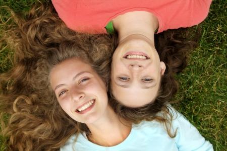 公園で草で横になっている 10 代の若者の友達に笑顔