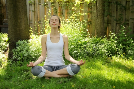 yoga meditation: Teenager relaxing and doing yoga in a nice and quiet garden Stock Photo