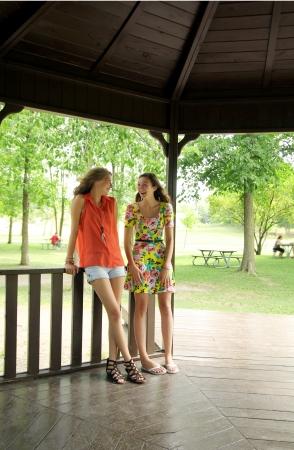 Two best friends teen talking in a gazebo in summer Stock Photo - 14726425