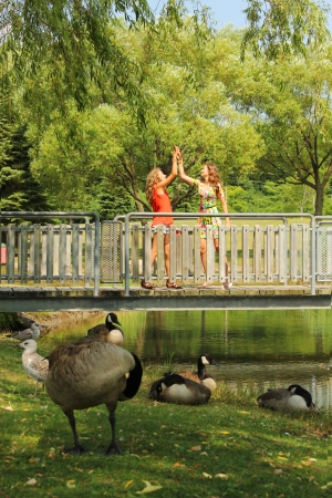 Teenager girl doing high 5 on a bridge by a nice summer day Stock Photo