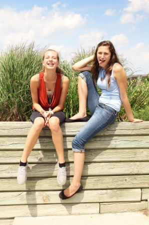 Two teenagers having fun on a wood wall photo