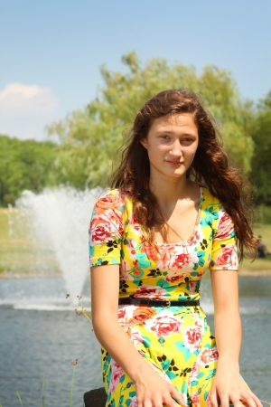 Teenager girl with a yellow flower dress in a park 写真素材