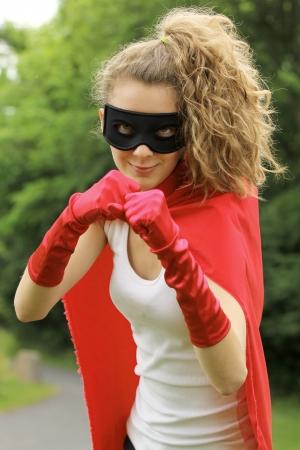 kracht: Blond gemaskerde meisje klaar om te vechten het dragen van een rode cape en rode handschoenen