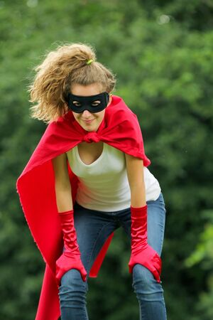 Serious blond and caucasian woman with a mask and red super hero kit photo