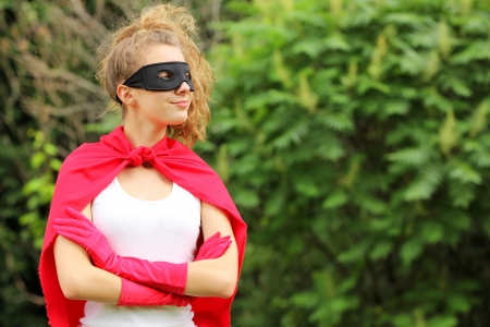 pretend: Blond girl wearing a red superhero uniform and a black mask smiling