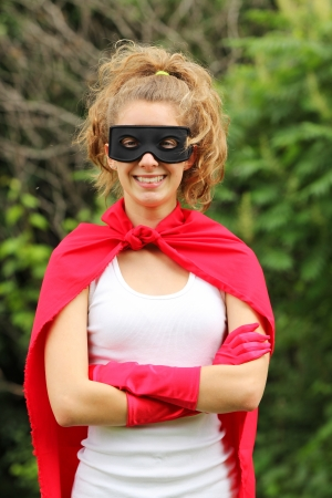 supergirl: Blond girl wearing a red superhero uniform and a black mask smiling